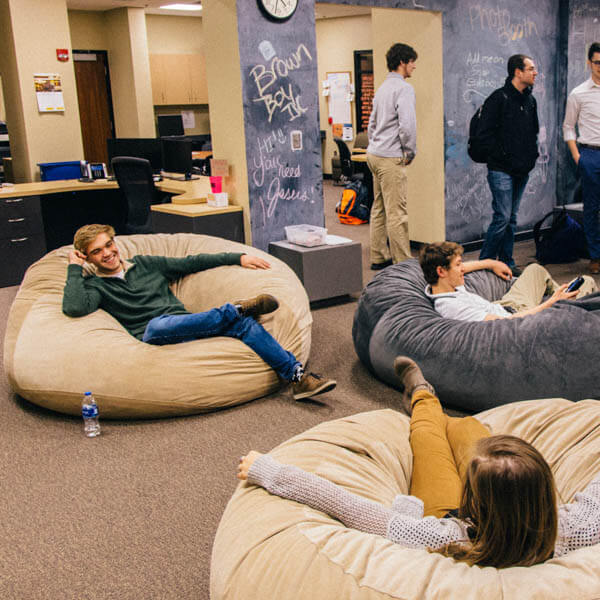 students relaxing and lying in lazy couch