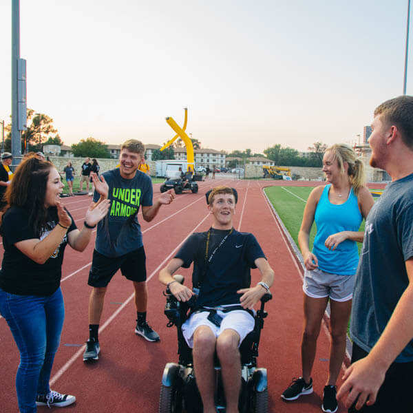 students helping with disabled student play in the Levis Track & Field